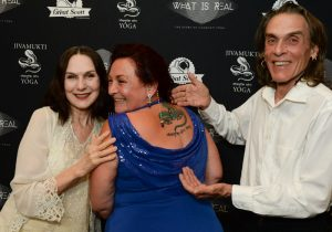 Sharon Gannon and David life with a student with Jivamukti Snake logo tattoo